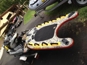 Jet ski with inflatable rescue sled that tracks with  the jet wake